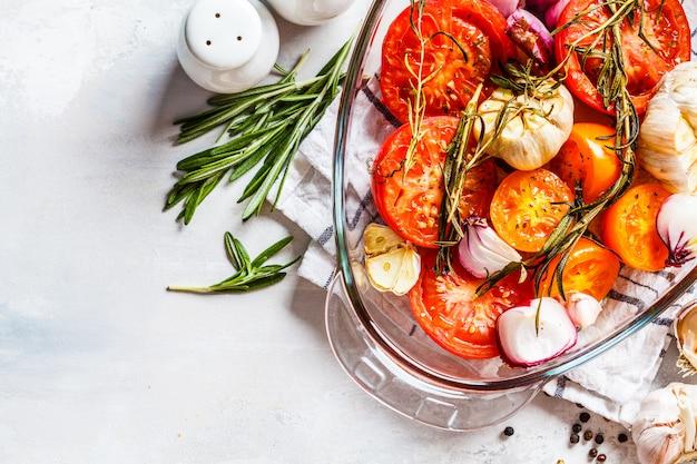 Tomates al horno con ajo, cebolla y romero en un plato de horno de vidrio, vista superior.