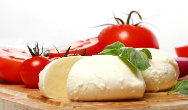 Tomates, albahaca y mozzarella sobre tabla de madera