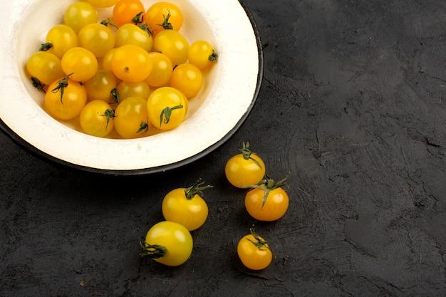 Tomates amarillos poco vitamina sabrosa fresca rica dentro y fuera de la placa blanca en un oscuro