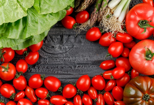 Los tomates se apilan con lechuga, espárragos, cebollas verdes en una pared de madera gris