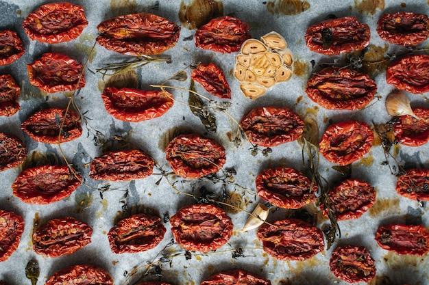 Tomates en bandeja para hornear, hierbas aromáticas, tomillo, básico, ajo y aceite de oliva.