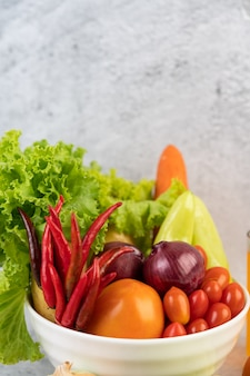 Tomates, cebollas rojas, pimientos, zanahorias y col china en una taza blanca en el piso de cemento.