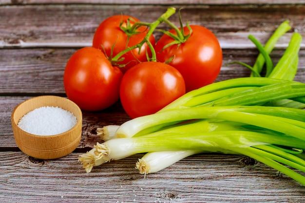 Tomates y cebolletas con sal sobre mesa de madera.