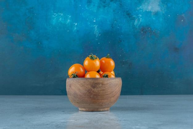 Tomates cherry amarillos en una taza de madera.