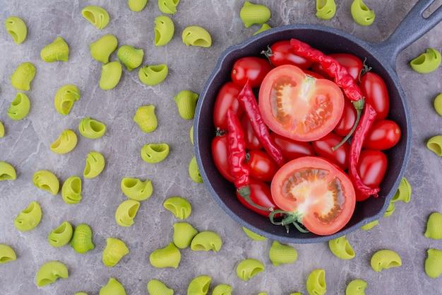 Tomates cherry y chiles rojos en una sartén negra con pastas verdes alrededor.