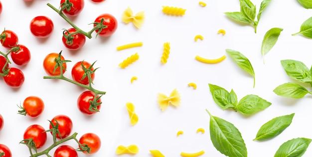 Tomates cherry con diferentes tipos de pasta y hojas de albahaca. concepto de comida italiana