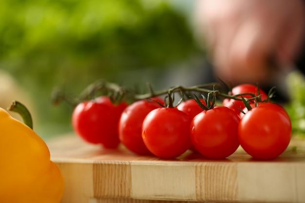 Los tomates cherry se encuentran en una tabla de cortar