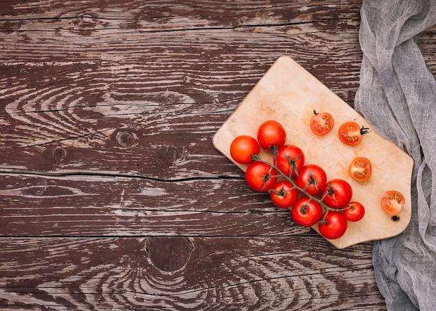 Tomates cherry enteros y cortados en tabla de cortar sobre el escritorio
