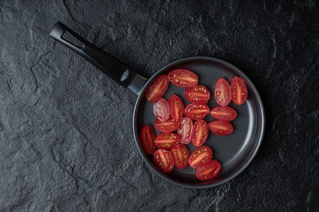 Tomates cherry frescos cortados a la mitad en una sartén negra sobre fondo negro.