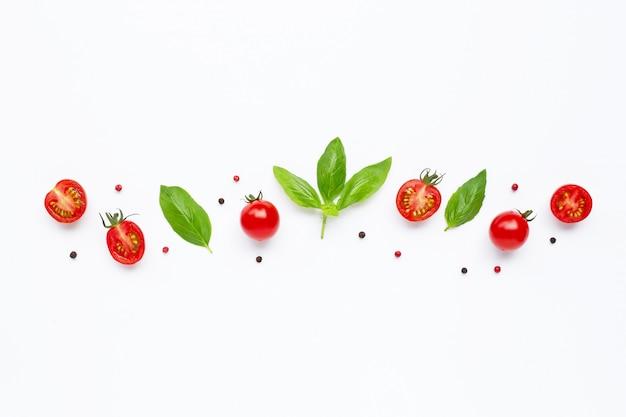 Tomates cherry frescos con hojas de albahaca y diferentes tipos de granos de pimienta en blanco vista superior