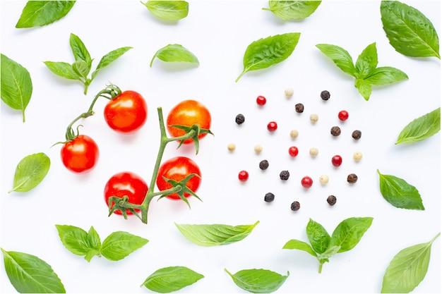 Tomates cherry frescos con hojas de albahaca y diferentes tipos de granos de pimienta en blanco