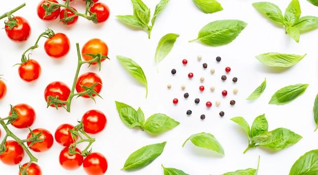Tomates cherry frescos con hojas de albahaca y diferentes tipos de granos de pimienta.