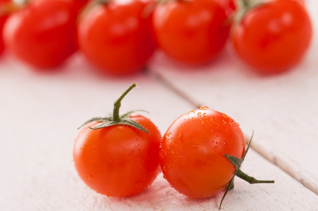 Tomates cherry frescos sobre una superficie blanca