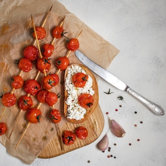 Tomates cherry a la parrilla en brochetas con bruschetta con tomate y queso, vista superior.