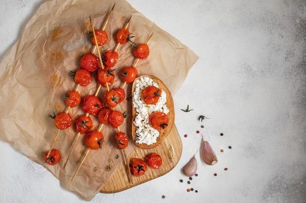 Tomates cherry a la parrilla en brochetas sobre papel de hornear