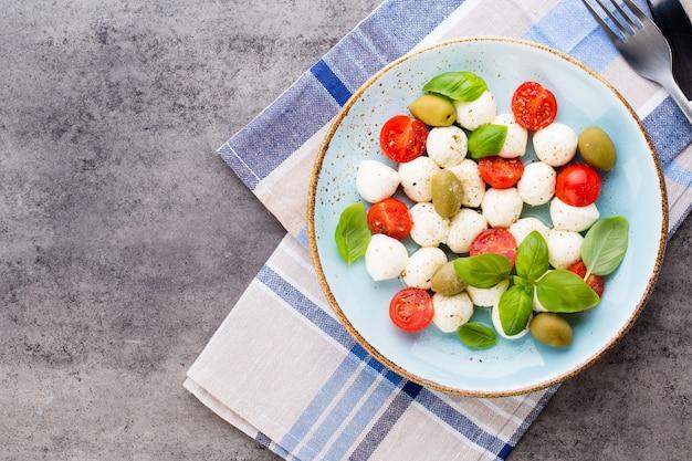 Tomates cherry, queso mozzarella, albahaca y especias en pizarra de piedra pizarra gris. ingredientes de la ensalada caprese tradicional italiana. comida mediterránea.