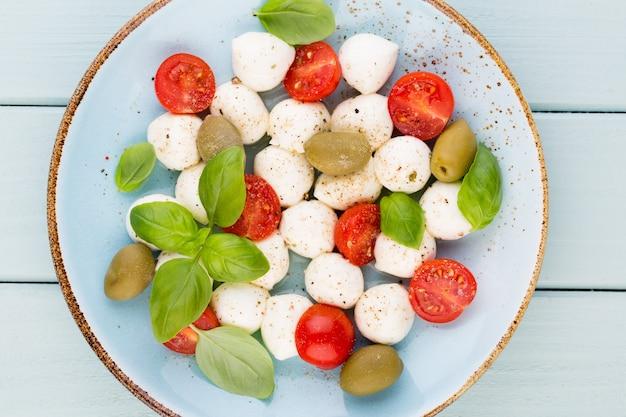 Tomates cherry, queso mozzarella, albahaca y especias en pizarra de piedra pizarra gris