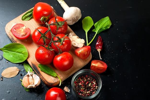 Tomates cherry en una rama, hojas de espinaca y especias