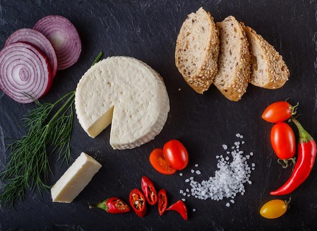 Tomates cherry rojos y amarillos en pizarra con rodajas de pan, cebolla, queso suave y sal