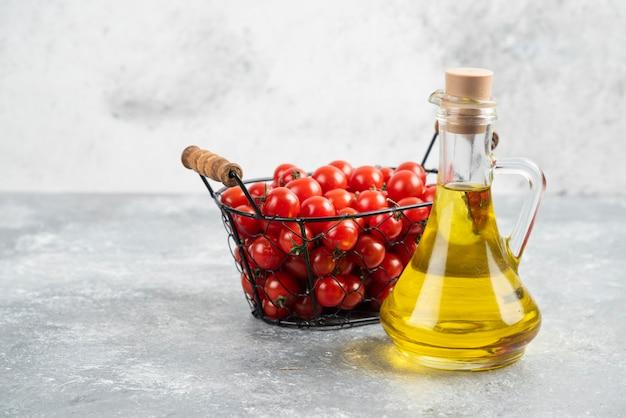 Tomates cherry rojos con una botella de aceite de oliva virgen extra sobre mesa de mármol.