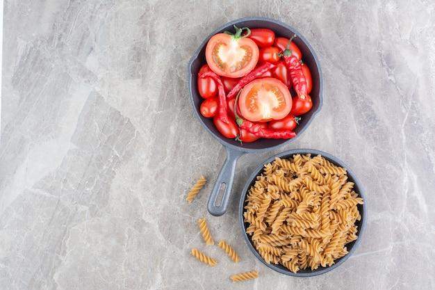 Tomates cherry rojos y chiles en una sartén con pastas alrededor.
