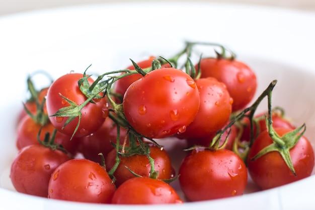 Tomates cherry rojos frescos maduros sobre un fondo blanco