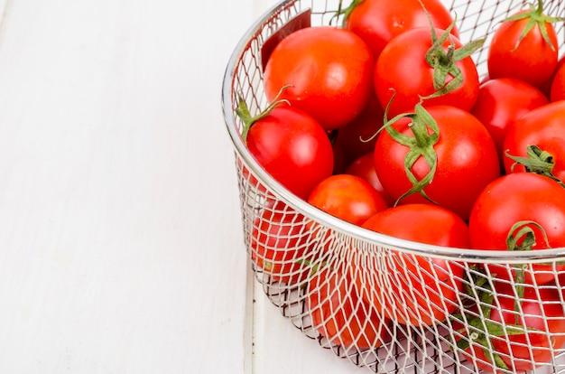 Tomates cherry rojos maduros en mesa de madera.