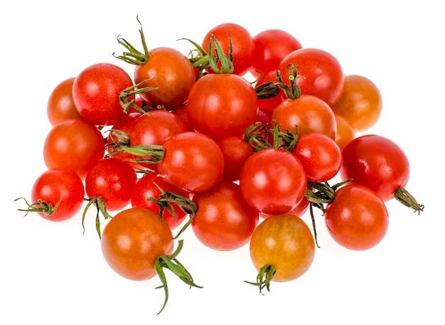 Tomates cherry rojos en miniatura sobre fondo blanco, productos vegetarianos y vegetales.