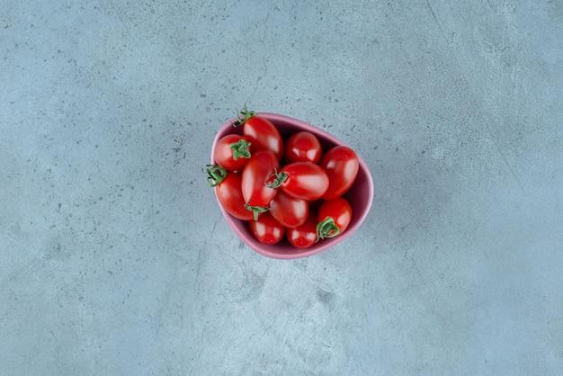 Tomates cherry rojos en una taza en azul.