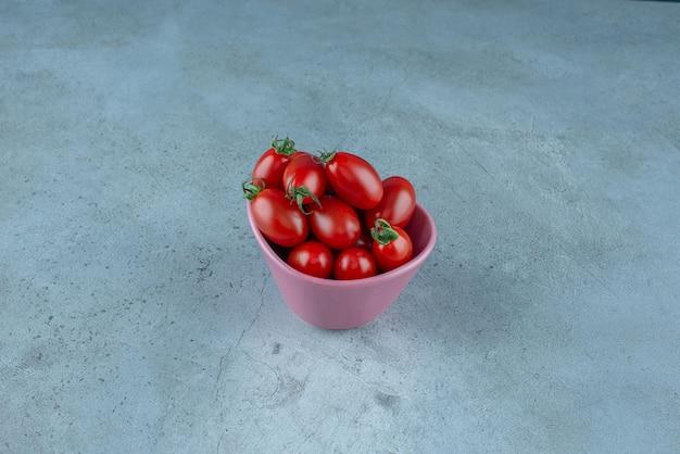 Tomates cherry rojos en una taza rosa.