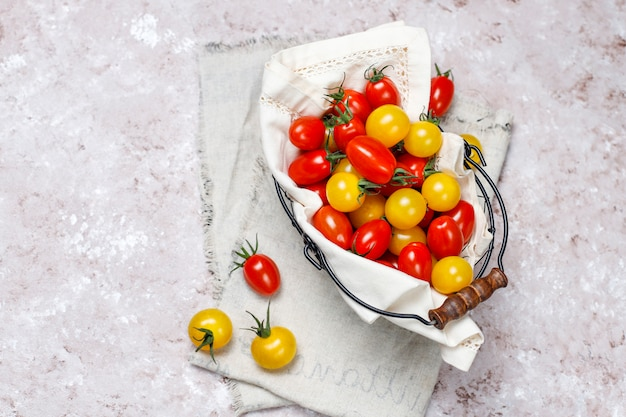 Tomates cherry de varios colores, tomates cherry amarillos y rojos en una cesta sobre fondo claro