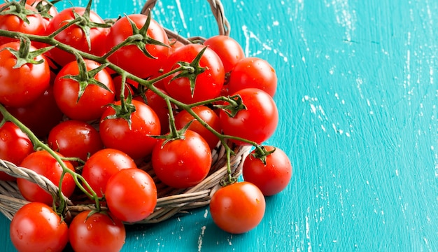 Tomates cherry en viejo fondo de madera turquesa