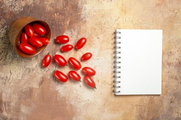 Tomates cherry de vista superior esparcidos del cuenco un cuaderno sobre fondo ámbar