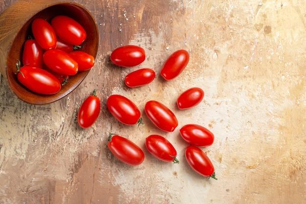 Tomates cherry de vista superior esparcidos del tazón sobre fondo ámbar
