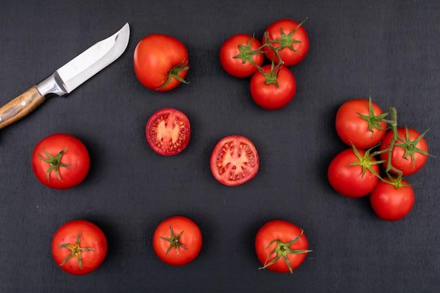 Tomates completos y medios y cerca del cuchillo sobre superficie negra