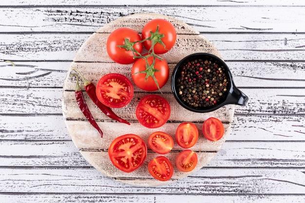 Tomates completos y medios en tablero blanco seco pimiento rojo picante aislado y pimienta negra en polvo en un tazón negro sobre superficie de madera blanca