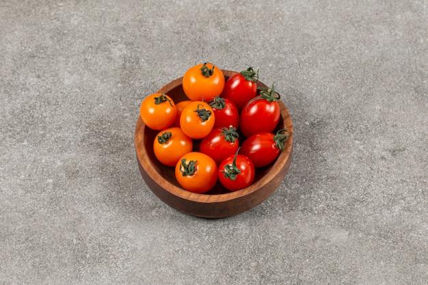 Tomates deliciosos en el cuenco, sobre el mármol.