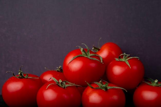 Tomates enteros en superficie morada