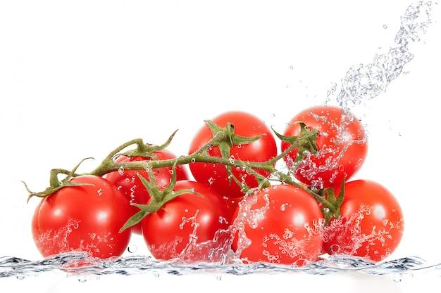 Tomates frescos cayendo en agua
