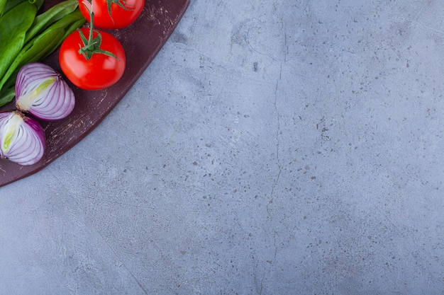 Tomates frescos y cebolla con verduras colocadas sobre tabla de madera.