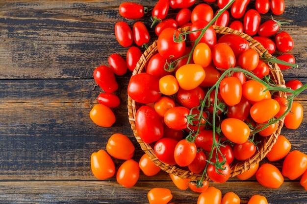 Tomates frescos en una cesta de mimbre plana yacía sobre una mesa de madera