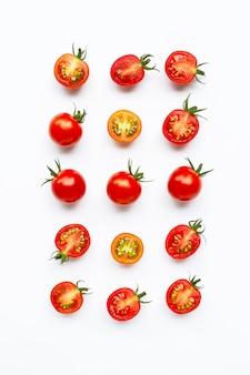 Tomates frescos, enteros y medio corte aislado en blanco.