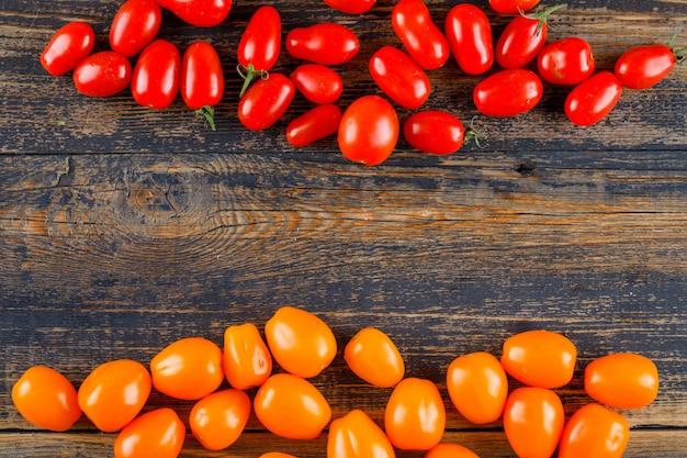 Tomates frescos en la mesa de madera, endecha plana.