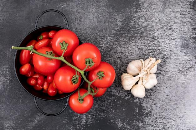 Tomates frescos en una olla y ajos