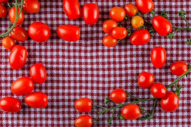 Tomates frescos planos sobre una tela de picnic