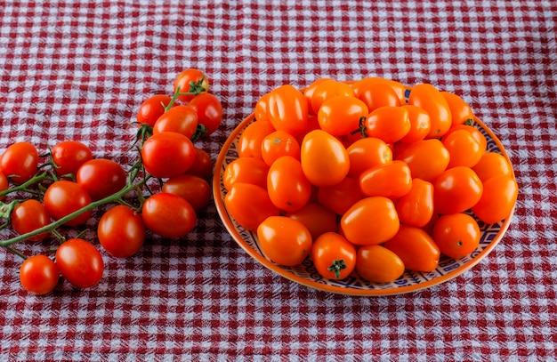 Tomates frescos en un plato sobre un paño de picnic.