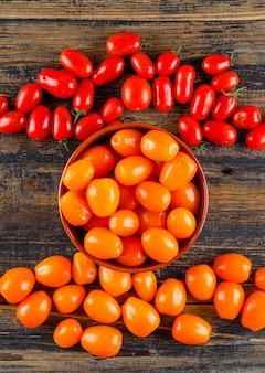 Tomates frescos en un recipiente sobre una mesa de madera. aplanada