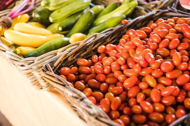 Tomates frescos rojos y calabacín orgánico en el mercado de verduras