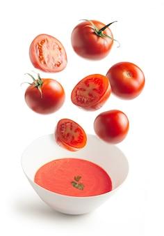 Tomates frescos volando y crema de tomate casera en un tazón