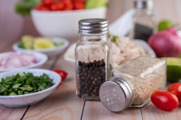 Tomates, junto con un frasco de semillas de sésamo, colocados sobre una mesa de madera.